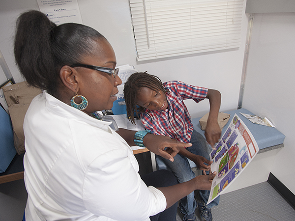Tammy Fordham Bell, a health educator in the School of Nursing's Delta-based school clinics, listens as Javarious Gilliam of Jonestown shows her the foods he eats on a chart of healthy fruits and veggies.