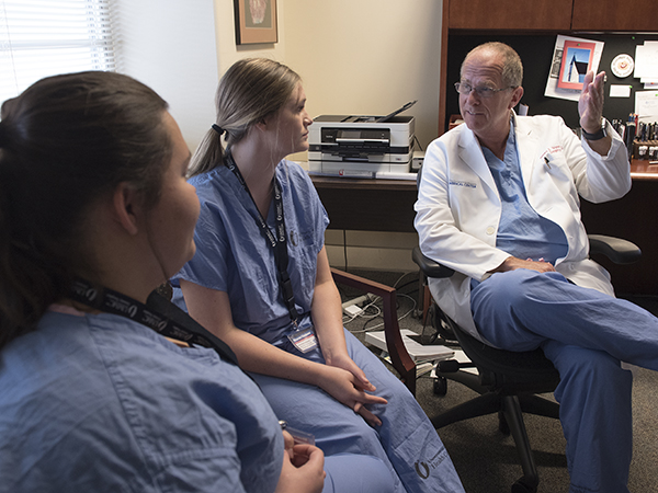 Dr. James J. Wynn, professor of transplant surgery, shares transplant surgery insights with Howell, left, and Blaylock.