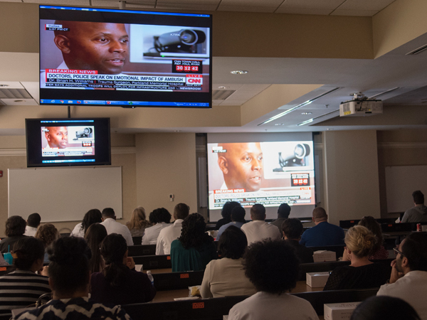 Lecture attendees watch a CNN recording of Williams' news conference.