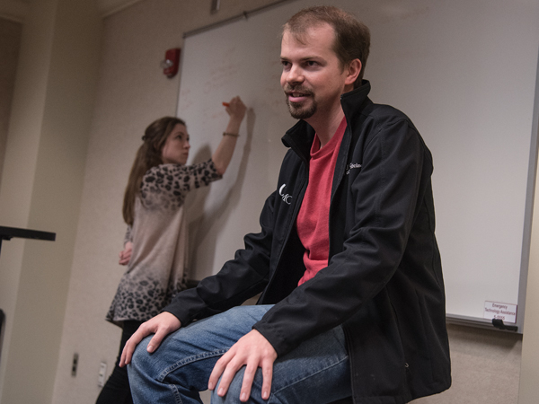 "During a meeting of Medical Spanish (Club de Espanol) co-president  R.J. Case, portraying a patient, describes his ""symptoms,"" as Mary Ball Markow lists them on the white board."