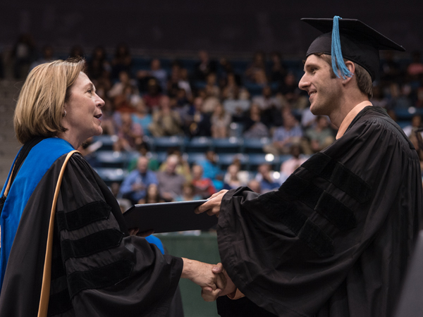 Dr. Jessica Bailey, dean of the School of Health Related Professions, gives a diploma to James Kimbrough, who earned the doctor of physical therapy degree and was honored with the Dr. Virginia Stansel Tolbert award as the student with the highest academic average in the School of Health Related Professions.