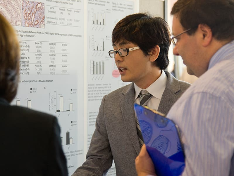 Marcelo Sakiyama, a fourth-year Ph.D. student in Pathology, shares his research with Dr. Damian Romero, assistant professor of biochemistry.