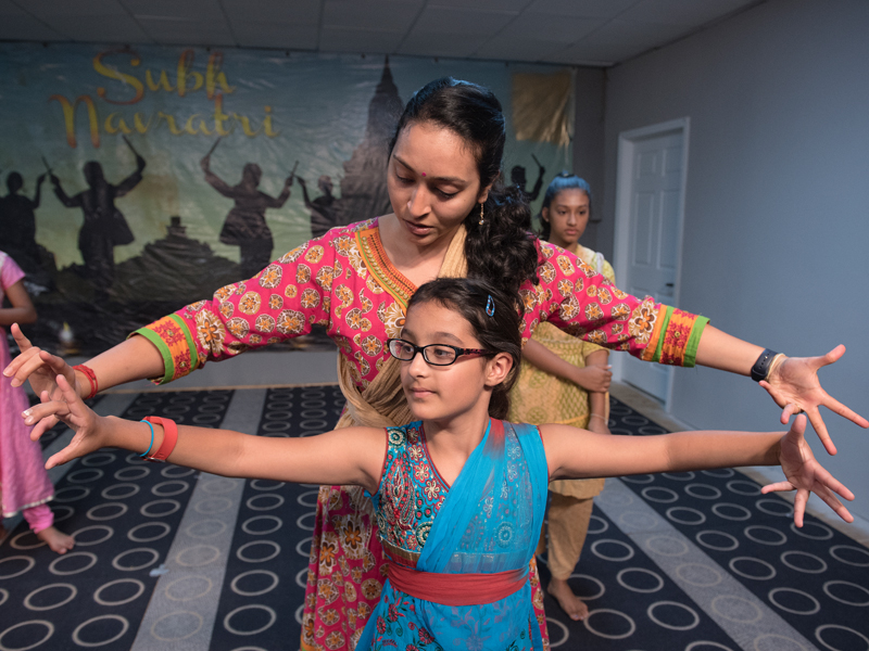 Deepti and student Shreya Tandon practice a dance move while rehearsing the traditional Indian dance Bharatnatyam for the upcoming Diwali festival celebration.