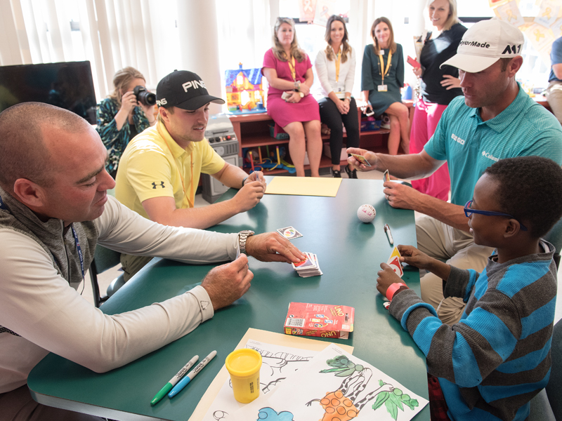 PGA golfers, from left, Ryan Armour, Austin Cook and Shawn Stefani fall victim to Batson Children's Hospital patient Keydarius Taylor's UNO skills during a visit Tuesday.