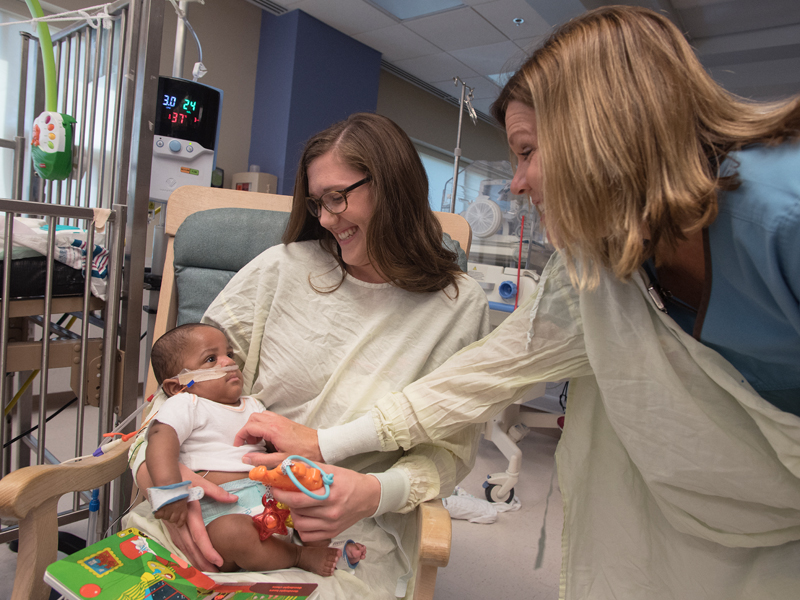 Katie McAuley, right,, an occupational therapist in Batson Children's Hospital, helps Rebecca Watson, OT2, obtain a smile from Christopher Bullock Bryant Jr., an NICU patient.