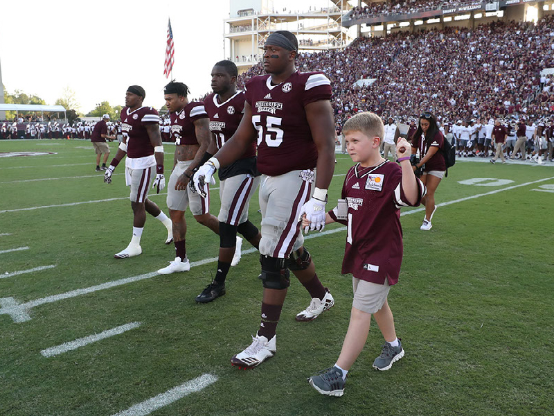 Kid Captain Thomas Blanks of Madison walks across Scott Field with Bulldogs at the Sept. 16 game against LSU.