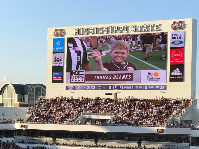 Kid Captain Thomas Blanks of Madison, a Bulldogs fan, is shown on the Jumbotron at Davis Wade Stadium ringing his cowbell.