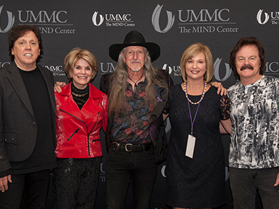 The Doobie Brothers held a meet and greet during to their concert. Pictured from left are John McFee, MIND Center Community Advisory Board Chair Suzan Thames, Pat Simmons, Vice Chancellor for health Affairs Dr. LouAnn Woodward and Tom Johnston.