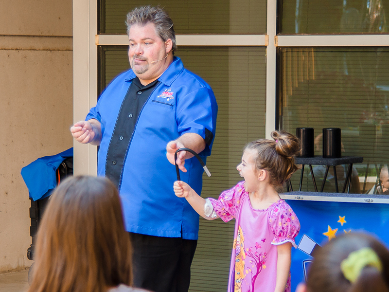 Dorian LaChance's magic trick gets a laugh from assistant Emma Reynolds of Petal, a Batson Children's Hospital patient.
