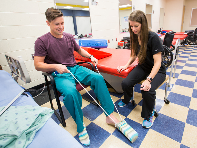 Audrey Hartman, a third year OT student, teaches classmate and simulated patient, Charles Nosco, how to put on his socks with the use of adaptive device. Nosco is simulating a patient who has had a hip replacement and is not allowed to bend over or pull knees up toward chest.