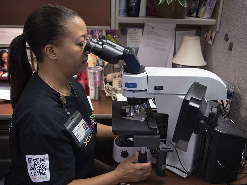 Sarah Short, cytotechnologist, reviews Pap test slides during the Jan. 28, 2017 See, Test & Treat event. The pathology team returns this year so women can receive readings the same day.