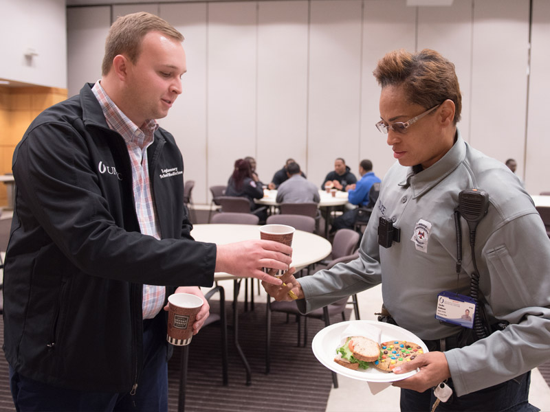 Logan Ramsey, ASB chief of staff, offers a beverage to Eureka Robinson, UMMC police officer, during Tuesday's appreciation lunch.