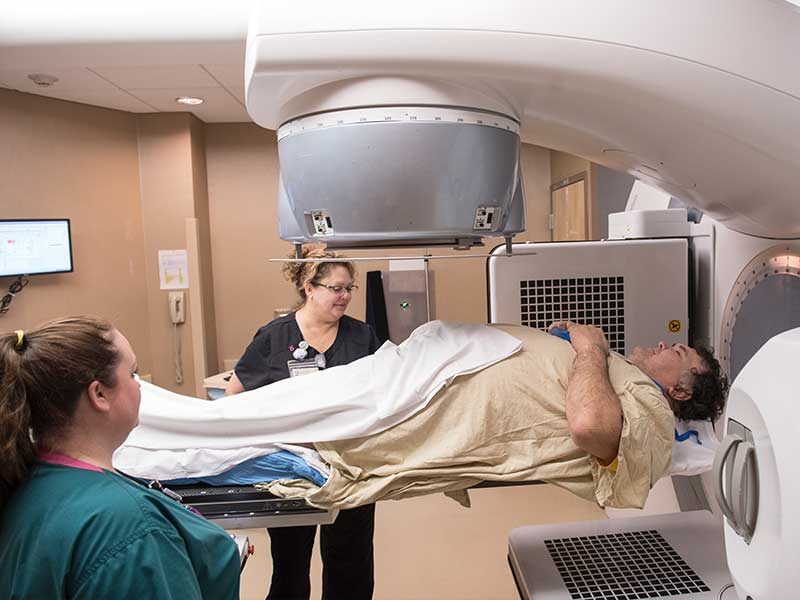 With assistance from radiation technologist Jessica Walters, left, and Kelly Salmons, Billy Jinks of Brookhaven receives radiation treatment for prostate cancer at the Medical Center's radiology oncology department.