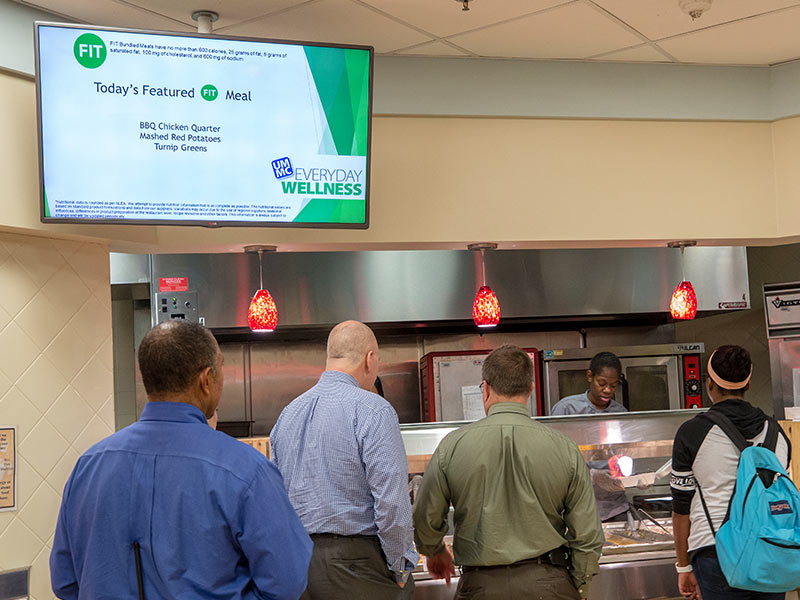 "Students and employees line up at the cafeteria's hot entree bar, where daily choices include a featured ""FIT"" meal meeting Everyday Wellness requirements for good nutrition."