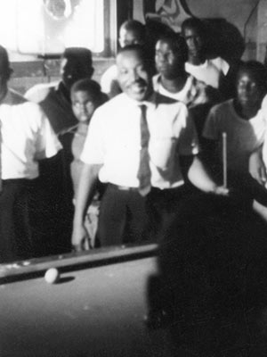 The Rev. Martin Luther King Jr. is surrounded by admirers in a Neshoba County pool hall, where he spoke about registering to vote and supporting the Mississippi Freedom Democratic Party, July 1964. (Photo used with the permission of the Rev. Ed King, University Press of Mississippi and the Mississippi Department of Archives and History)
