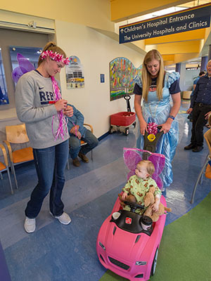 Ole Miss softball players Brittany Finney, left, and Alex Schneider give Batson Children's Hospital patient Emma Grace Simpson of Hattiesburg a ride in her pink convertible during a hospital visit Tuesday.
