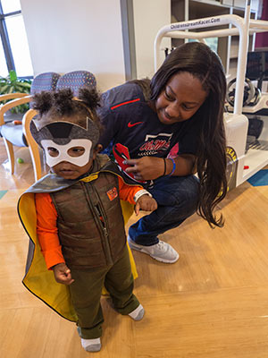 Ole Miss softball player Elantra Cox and Children's of Mississippi patient Nasi Rai Strickland play superhero during Cox's visit to Batson Children's Hospital.