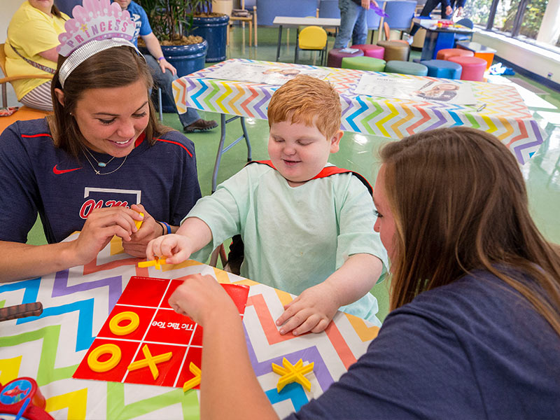 Ole Miss softball players Paige McKinney and Alyssa Clayton play tic-tac-toe with Batson Children's Hospital patient Blake Stone of Philadelphia.