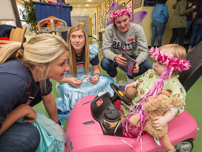 Ole Miss softball players, from left, Kaitlin Lee, Alex Schneider and Brittany Finney share princess finery with Batson Children's Hospital patient Emma Grace Simpson of Hattiesburg.