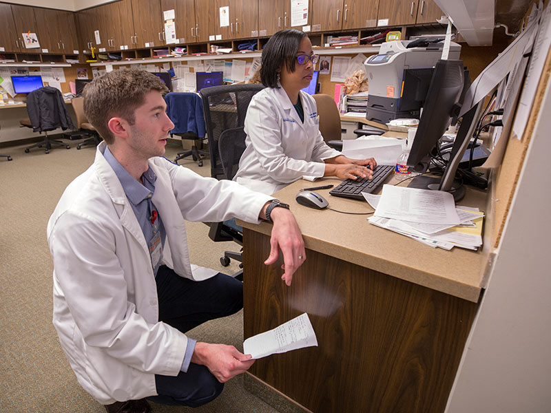 Fourth-year medical student Kyle Lacy and Dr. Kimberly Bibb, assistant professor of family medicine, use Epic to electronically record information on the patients they treat.