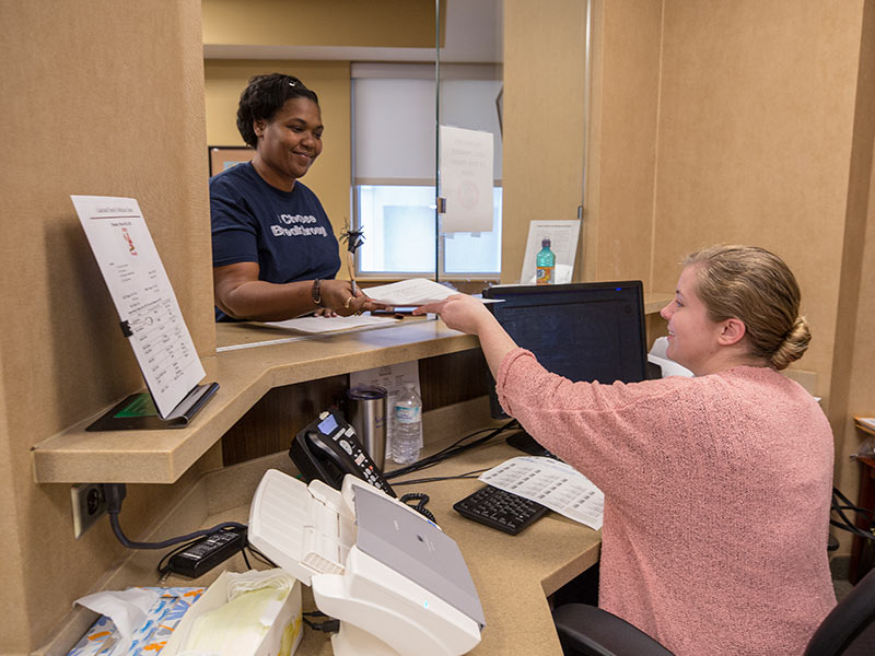 Patient Nikki McInnis of Jackson, left, is checked in for her appointment in the Department of Family Medicine by administrative assistant April Little.