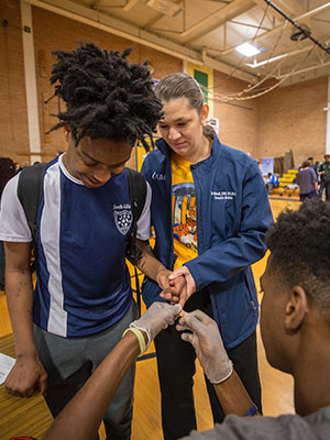 Josie Bidwell gives Kevin Fox moral support as he gets a blood glucose screening from Keyontravious Thompson.