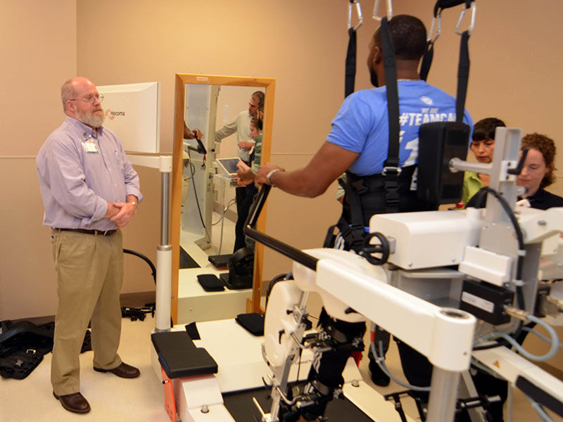 Dr. Keith Tansey, UMMC professor of neurosurgery; and Methodist Rehab employees Tremaine Nathan, assistive technology specialist; physical therapist Patricia Oyarce; and research physical therapist Annie Rieher train on a gait rehabilitation system in Methodist Rehabilitation Center's neurorobotics laboratory.