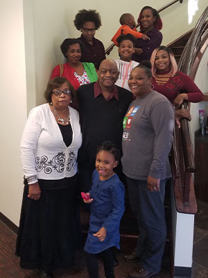 Jones, center, is surrounded by family members including his wife, Emma, wearing a white sweater.  Standing on the other side of Abram Jones is Lywanda White.