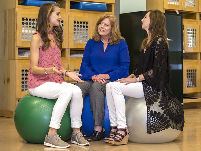 "Dr. Lisa Barnes, center, chair of the physical therapy program, calls Green, right, ""the bravest person I know,"" while Seal simply says Green is ""an inspiration."""