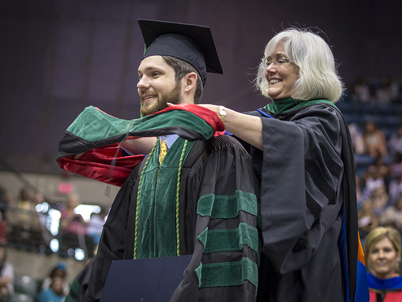 New School of Medicine graduate Stephen Wahl is hooded by his mother, Dr. Nancy Wahl, associate professor of pediatric emergency medicine.