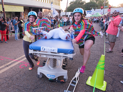 Nurses representing Telehealth including Kourtland Adams, Megan Duet and Terri Morgan take part in a gurney race to celebrate 2016 National Nurses Week.