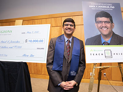 Janorkar, the 2018 Regions TEACH Prize winner, is framed by a ceremonial check and a congratulatory poster.