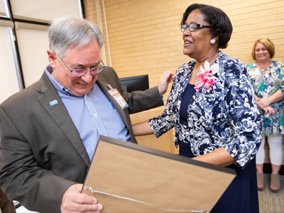 Dr. Ralph Didlake, associate dean for academic affairs, presents Triplett with a citation from UMMC for her years of service.