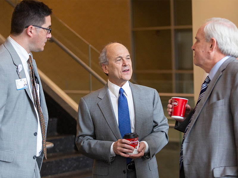 Dr. Peter Arnold, left, and Dr. Michael Henderson, right, chat with Chassin during a meeting with UMMC administrators.