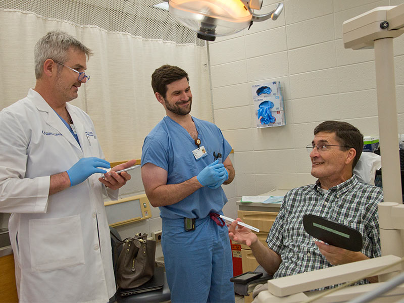 As School of Dentistry resident Walter Moses (center) assists, Dr. Ron Caloss, associate professor of oral and maxillofacial surgery, asks patient Smith to look at his teeth in a mirror shortly after Caloss clipped wires that had held Smith's jaws shut.