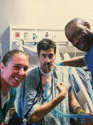 While still hospitalized, Smith is pictured with two of his UMMC caregivers, physical therapist Kirby Smith, left, and occupational therapist Marcus Harris.