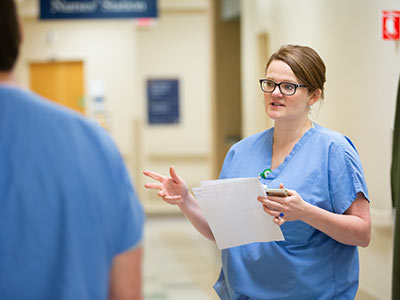 Dr. Meagan Mahoney confers with one of her colleagues near a nurses' station.