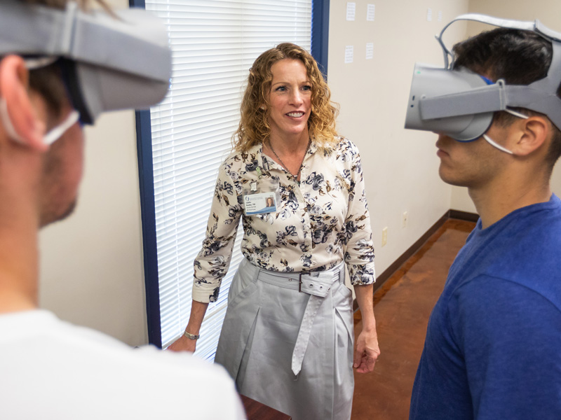 Dr. Jennifer Reneker, associate professor of physical therapy, watches as soccer players Victor Bazan and Jorge Fernandez play a virtual reality game in which they track a flying fish without moving their heads.
