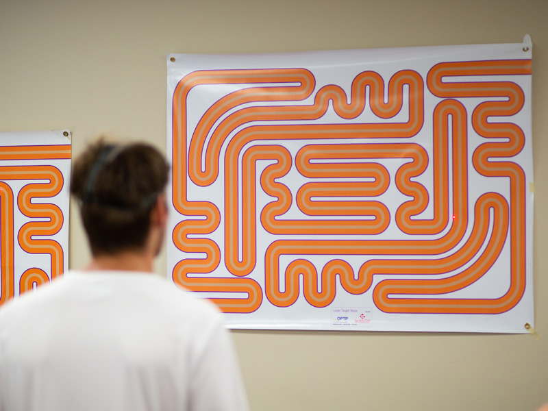 A Mississippi College soccer player uses a head-mounted laser to trace the path of a maze in an exercise designed to gauge eye control.