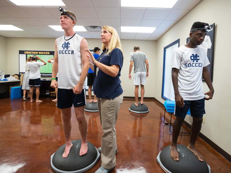Dr. Kimberly Willis, associate professor of physical therapy, positions soccer players Cameron Allcorn, left, and Cayman Pearson on rubber stands that impact their balance as she prepares them for their next motor skills test.