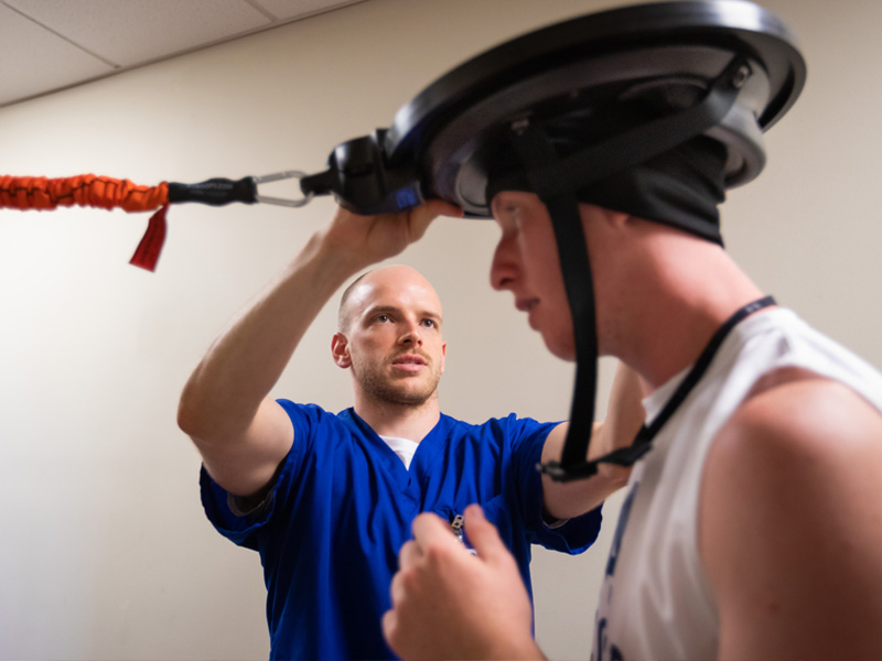Tyler Luchtefeld, a physical therapy resident, affixes a device to the head of soccer player Cameron Allcorn as part of testing their reflexes and motor skills.