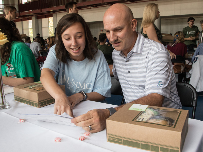 First-year medical student Maggie Dickerson, left, reviews a schedule of afternoon events with her father Guy.