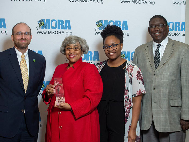 Doris Whitaker, second from left, is MORA's Community Faith Leader or Chaplain of the Year. She's pictured with, on left, MORA chief business officer Russell Touchet; her daughter, Eryn Whitaker; and the Rev. Timothy T. Scott, her pastor at Harvest Celebration Evangelistic Church, where she serves as associate pastor of worship.