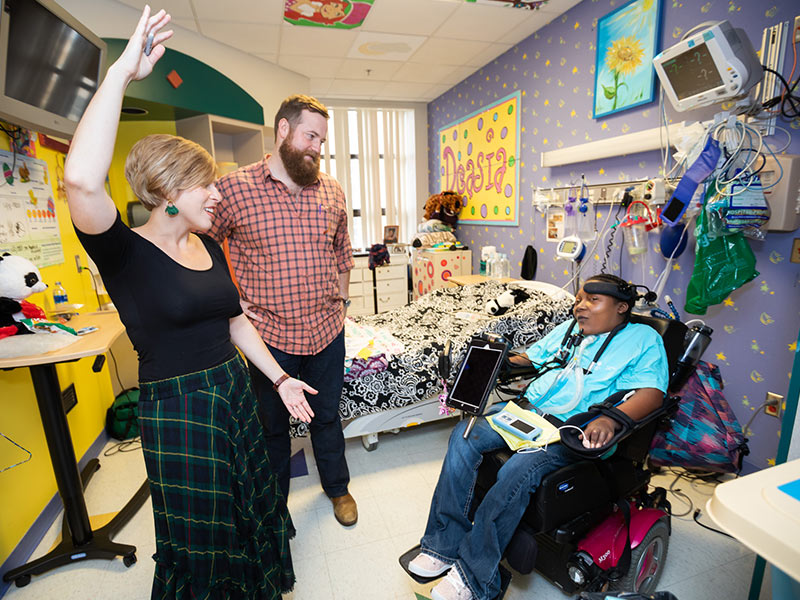Erin and Ben Napier, getting a tour of Batson Children's Hospital before speaking at the Sanderson Farms Championship Women's Day luncheon, visit with patient DeAsia Scott.