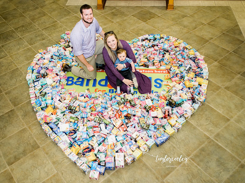 Mark and Paige Welch and their son, Jack, show some of the many bandages collected through their Band-Aids for Batson campaign. (Photo courtesy of Taylor Cooley Photography.)