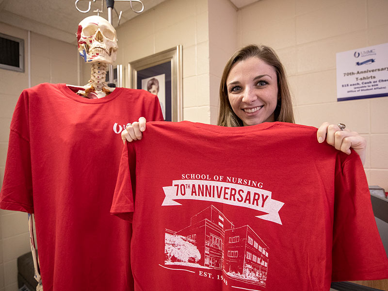 Carson Williams, senior and student ambassador in the School of Nursing, shows off the anniversary T-shirt.