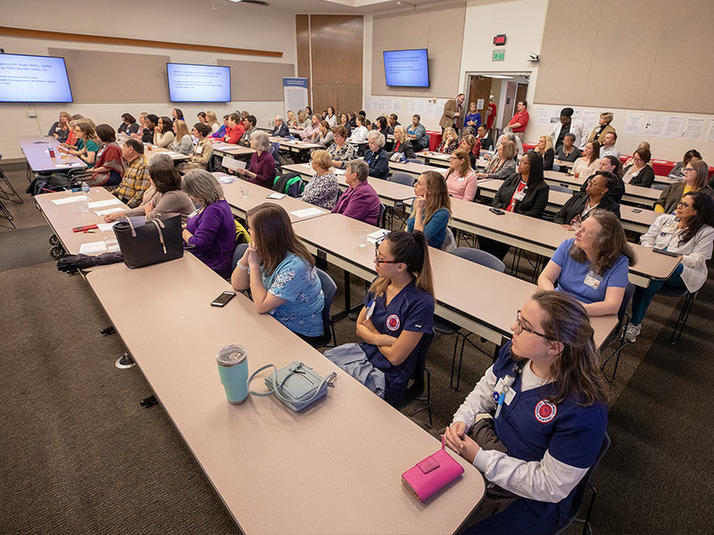 Attendees of the School of Nursing's 70th anniversary listen to remarks from Medical Center Vice Chancellor LouAnn Woodward, former Vice Chancellor and Dean of the School of Medicine James Keeton and Dean of the School of Nursing Kim Hoover.