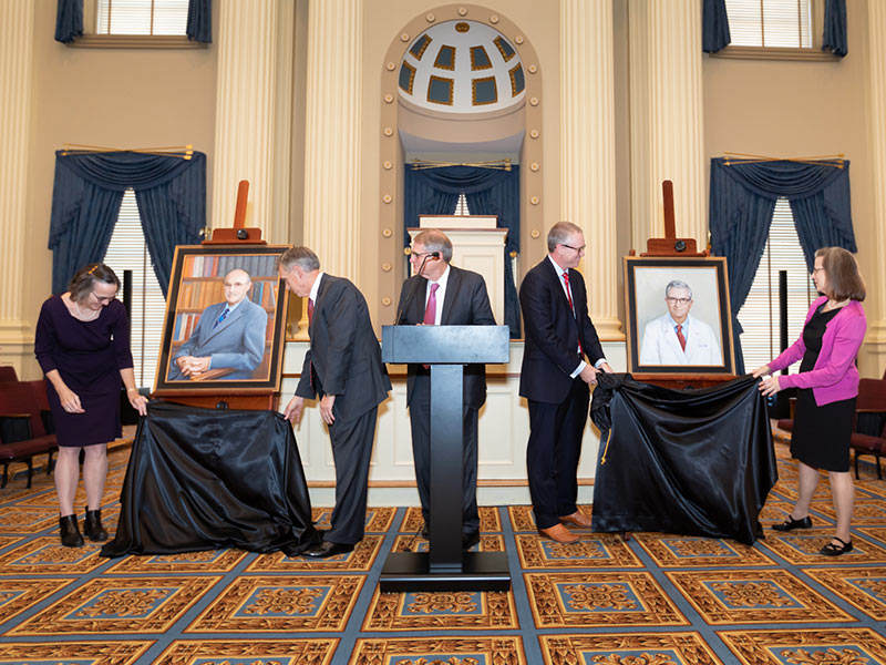Kane Ditto, at podium, oversees the unveiling of the portraits of Dr. Arthur Guyton, left, beside Dr. Jean Gispen and Dr. John Hall, and Dr. James Hardy beside Dr. Chris Anderson and Dr. Bettie Winn Hardy Story.