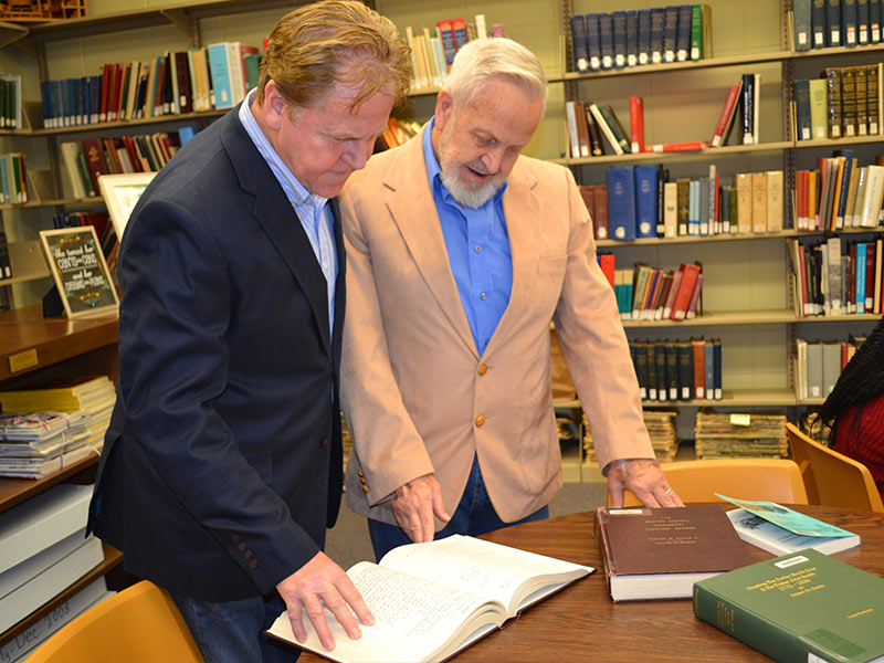 During a recent visit to UMMC, Wayne Lee, left, and John Lee examine historical documents related to the asylum that had housed their grandfather, John Benedict Whitfill.