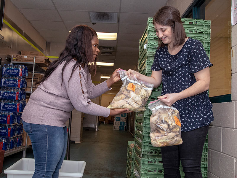 Jasmine Ware, left, and Mariam Ebeid start packing up leftovers they'll drive from the cafeteria loading dock to the kitchen at Stewpot.